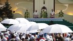 People standing under white umbrellas