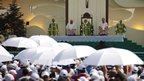 People standing under white umbrellas