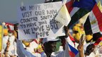 Man holding poster saying 'We hope you visit our new country South Sudan to have your blessing. We love you Pope""
