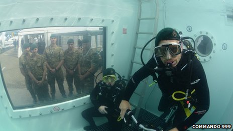 Marines watch Chris Sirett and Brian Stokes through a window as they attempt the underwater challenge