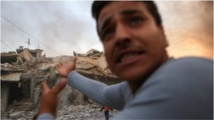 A man points towards a bombed house in Aleppo, Syria