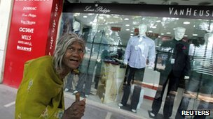 A beggar walks past a shop window with designer clothes in New Delhi's main business district in this October 29, 2009 file photo