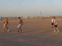 Military personnel play football in Afghanistan