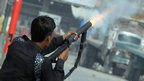 A Pakistani policeman fires tear gas at protesters near the US consulate during in Karachi, 17 September 
