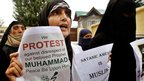 A woman holds placards as she shouts slogans during a protest in Srinagar, Indian-administered Kashmir (17 Sept 2012).