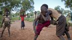 Boys gather to wrestle on a sandy patch of ground in Yida camp, South Sudan