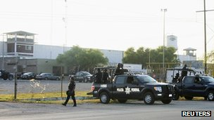 Police stand outside a jail after the escape of more than 130 inmates in Piedras Negras