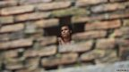 A Buddhist monk is pictured through a hole in a wall at a monastery in Burma