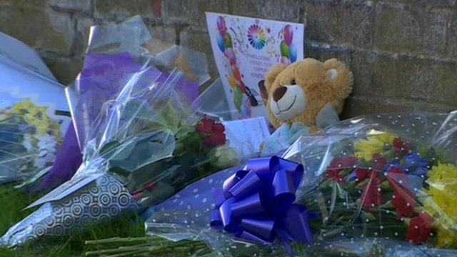 Floral tributes are laid close to where the three family members died.
