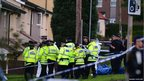 Police officers gather at the scene where two female police officers were fatally wounded while responding to a call in Hattersley, Greater Manchester, north-west England
