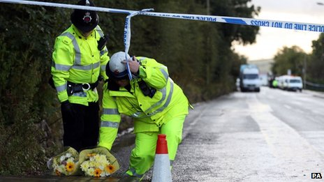 Police officers collect flowers at the scene of the Mottram shootings