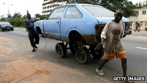Two men pushing a car in Accra