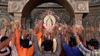 Indian devotees raise their hands as they pray in front of an idol of elephant-headed Hindu God Ganesh in Ahmedabad, India