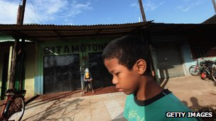 Boy walking down street in rural Brazil