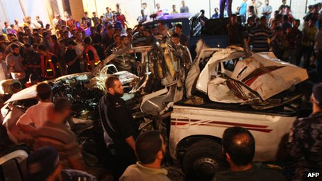 People gather around the wreckage of a car targeted in an Israeli air strike in Rafah, Gaza 19 September 2012