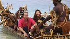 The Duke and Duchess of Cambridge sitting in a canoe being rowed by people from Guadalcanal in traditional dress
