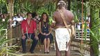 The Duke and Duchess of Cambridge sit listening to a man in traditional dress giving a speech in the foreground