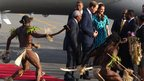 The Duke and Duchess of Cambridge arrive in the Solomon Islands, and are greeted by warriors in traditional dress dancing