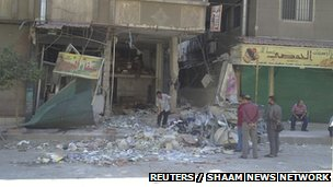 "Residents look at a damaged store after clashes between the Free Syrian Army and forces loyal to Syria""s President Bashar al-Assad in Damascus September 15, 2012"