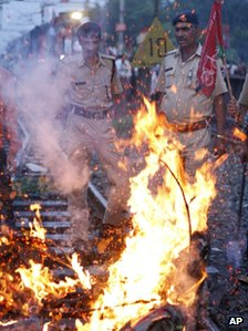 Indian railway policemen stand near a burning effigy representing the Indian government during a protest along railway tracks in Allahabad, India, Thursday, Sept. 20, 2012