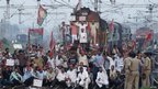Samajwadi Party activists hold party flags and block a railway track during a protest in Allahabad