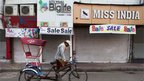 A rickshaw driver pedals past closed shops as he looks for passengers at Lajpat Nagar market in Delhi