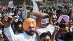 Former Indian cricketer and opposition Bharatiya Janata Party MP Navjot Singh Sidhu along with supporters shout-slogans as they carry LPG gas canisters during a demonstration in Amritsar