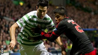 Celtic striker Miku makes his way past Melgarejo (right)