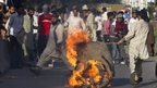 Man dragging burning piece of canvas in Islamabad