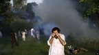 Man rubbing eyes after tear gas exposure in Islamabad