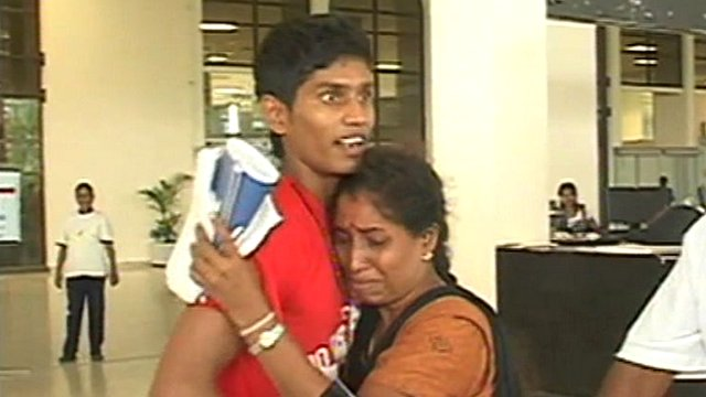 Sri Lankan woman greeting son with hug