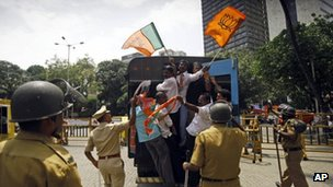 "India""s main opposition Bharatiya Janata Party activists wave party flags as they are detained by police during a protest in Mumbai"