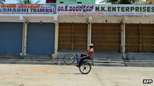 An Indian boy bikes past closed shops during a nationwide strike in Bangalore