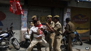 Indian police officers detain a left party activist during a nationwide strike in Hyderabad