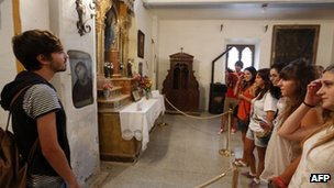 Visitors look at the fresco restored by Cecilia Gimenez