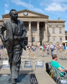 A statue of Harold Wilson in front of Huddersfield's railway station, a listed building