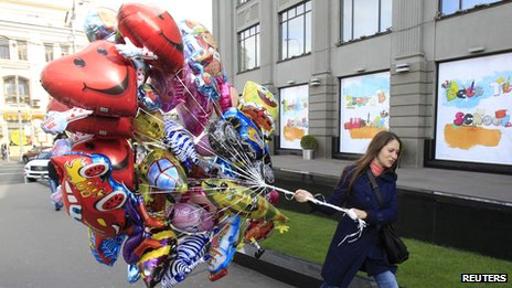 Woman in city street with bunch of balloons