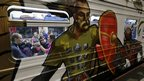 People travel in a commuter train decorated with graffiti depicting episodes of Russian history