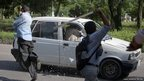Protesters use sticks to smash the windscreen and windows of a car during an anti-America protest march in Islamabad.