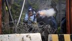 A Pakistani police officer fires tear gas canister at protesters in Islamabad. Photo: 21 September 2012