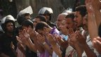 People pray in front of riot police in Cairo, Egypt. Photo: 21 September 2012