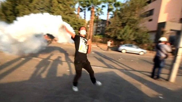 Protester throws smoke bomb