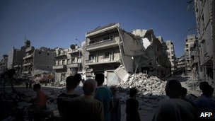 Syrian men look at the destroyed building of a school which was bombed by Syrian government war planes which was allegedly housing rebel fighters in the Bustan al-Qasr neighbourhood of Aleppo 