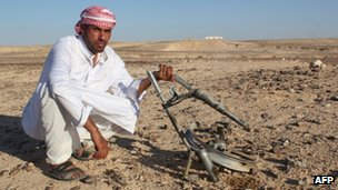 An Egyptian Bedouin shows the pieces of metal at the scene of an explosion on 26 August 2012.