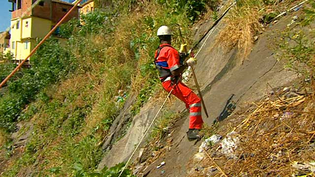 Man abseiling to collect rubbish