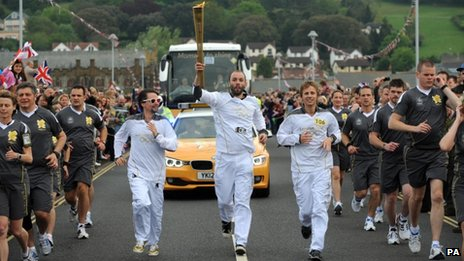 Matt Bellamy, Dominic Howard and Christopher Wolstenholme, Muse, carry the Olympic flame on the leg between Torquay and Teignmouth
