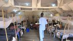 Nurse Juma James walking in a tent ward in Aweil Hospital, South Sudan