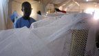 Nurse Juma James pictured behind a mosquito net in Aweil Hospital, South Sudan