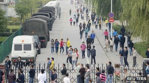 Workers walk past paramilitary police vehicles outside the Foxconn plant