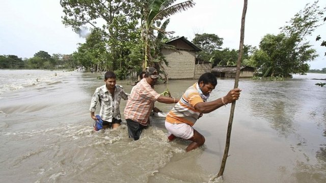 Villagers cross a flooded road at Lachi Bishnupur village in the northeastern Indian state of Assam September 22, 2012. 